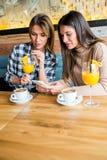 2 молодых женских друз сидя в кафе Стоковое Изображение