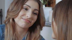 2 молодых женских друз сидя на софе в живущей комнате и gossiping видеоматериал