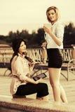 2 молодых женщины моды используя планшет внешний Стоковые Изображения RF