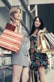 2 молодых женщины моды с хозяйственными сумками в моле Стоковое Изображение RF