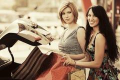 2 молодых женщины моды с хозяйственными сумками на автостоянке автомобиля Стоковая Фотография RF