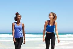 2 молодых женщины спорт смеясь над на пляже после разминки Стоковые Фотографии RF