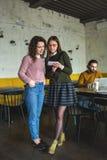 2 молодых женщины с smartphone и таблеткой в кафе Стоковое фото RF