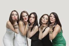 5 молодых женщин дуя поцелуи над серой предпосылкой Стоковые Изображения RF