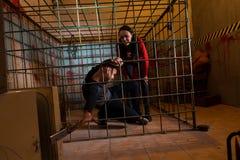 2 молодых жертвы хеллоуина заключенной в турьму в клетке металла, тяге мальчика Стоковое Изображение