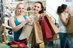 2 молодых жизнерадостных девушки ходя по магазинам совместно Стоковые Фотографии RF
