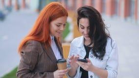 2 молодых изумительных бизнес-леди связывая и смеясь над на городской улице, замедленном движении Steadicam кофе утра акции видеоматериалы