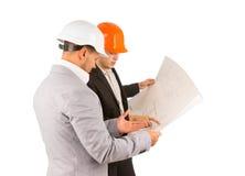 2 молодых инженера обсуждая план здания Стоковые Фото