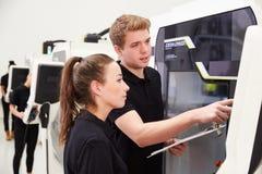2 молодых инженера работая машинное оборудование CNC на поле фабрики Стоковое Изображение RF