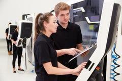 2 молодых инженера работая машинное оборудование CNC на поле фабрики Стоковая Фотография RF