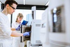 2 молодых исследователя унося эксперименты в лаборатории Стоковое Изображение