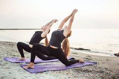 2 молодых кавказских женщины практикуя йогу на пляже Стоковая Фотография RF