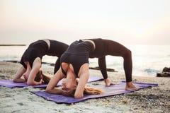 2 молодых кавказских женщины практикуя йогу на пляже Стоковое фото RF