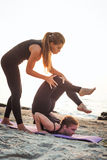 2 молодых кавказских женщины практикуя йогу на пляже Стоковое Изображение