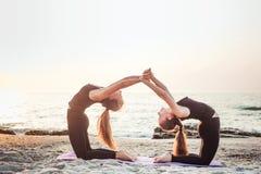 2 молодых кавказских женщины практикуя йогу на пляже Стоковые Фото