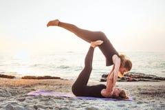 2 молодых кавказских женщины практикуя йогу на пляже Стоковые Фотографии RF