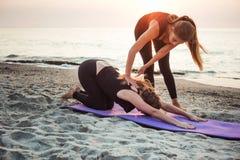 2 молодых кавказских женщины практикуя йогу на пляже Стоковая Фотография