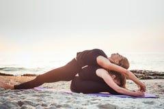 2 молодых кавказских женщины практикуя йогу на пляже Стоковые Изображения