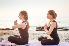 2 молодых кавказских женщины практикуя йогу на пляже Стоковые Изображения RF