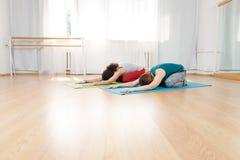 2 молодых кавказских женщины разрабатывая в центре йоги Стоковые Изображения