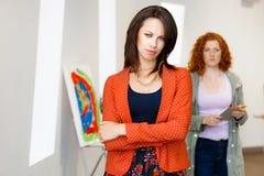 2 молодых кавказских женщины стоя в художественной галерее Стоковая Фотография