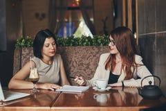2 молодых кавказских коммерсантки с компьтер-книжкой Женщины в кафе Стоковые Изображения