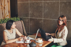 2 молодых кавказских коммерсантки с компьтер-книжкой, тетрадью Женщины в кафе Стоковая Фотография