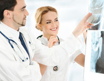 2 молодых кавказских доктора рассматривая рентгеновские снимки Стоковая Фотография