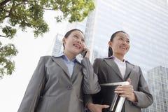 2 молодых коммерсантки идя вниз с улицы и говоря на телефоне Стоковая Фотография