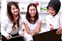 3 молодых коммерсантки обсуждая о их новом проекте Стоковое Изображение