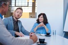 3 молодых коллеги говоря стратегию во время встречи офиса Стоковое Изображение
