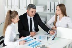 2 молодых красивых бизнес-леди советуя с с их colleag Стоковая Фотография RF