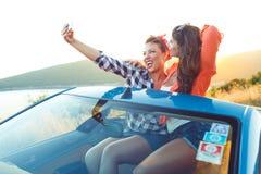 2 молодых красивых девушки делают selfie в автомобиле с откидным верхом Стоковые Фотографии RF