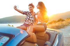 2 молодых красивых девушки делают selfie в автомобиле с откидным верхом Стоковое Изображение