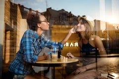 2 молодых красивых девушки усмехаясь, говорить, отдыхая в кафе Снятый от внешней стороны Стоковая Фотография RF