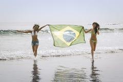2 молодых красивых женщины в бикини на пляже бежать с Бразилией сигнализируют Стоковое Изображение RF