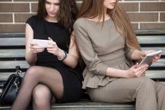2 молодых красивых женщины сидя на стенде Стоковое фото RF