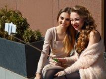 2 молодых красивых счастливых женщины делая selfie outdoors Стоковая Фотография