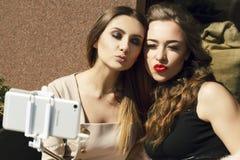 2 молодых красивых счастливых женщины делая selfie outdoors Стоковое Изображение RF