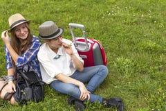 2 молодых милых девушки сидя в луге пока путешествующ Стоковые Изображения