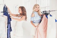 2 молодых милых девушки смотря платья и пробуют дальше его пока выбирающ на магазине Стоковое Фото
