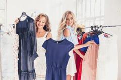 2 молодых милых девушки смотря платья и пробуют дальше его пока выбирающ на магазине Стоковые Изображения