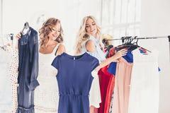 2 молодых милых девушки смотря платья и пробуют дальше его пока выбирающ на магазине Стоковое фото RF