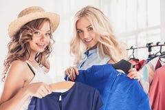 2 молодых милых девушки смотря платья и пробуют дальше его пока выбирающ на магазине Стоковое Изображение