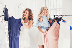 2 молодых милых девушки смотря платья и пробуют дальше его пока выбирающ на магазине Стоковые Изображения RF