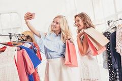 2 молодых милых девушки смотря платья и пробуют дальше его пока выбирающ на магазине Стоковое Изображение RF