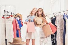 2 молодых милых девушки смотря платья и пробуют дальше его пока выбирающ на магазине Стоковая Фотография