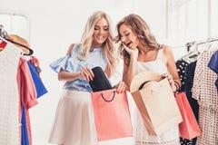 2 молодых милых девушки смотря платья и пробуют дальше его пока выбирающ на магазине Стоковые Фото