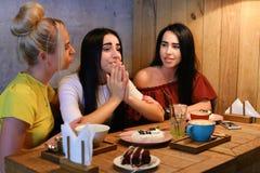 3 молодых милых подруги девушки тараторят, злословящ, secr доли Стоковое фото RF