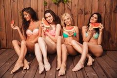 4 молодых милых смешных девушки есть арбуз Стоковые Фото
